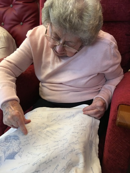 Jean finding the signatures of her two sisters, Myra and Betty, and herself on a millennium tea towel from Ferryhill Church