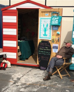 Man enjoying the Lobster Hatchery tea towel at North Berwick - selling from the Beach Huts!